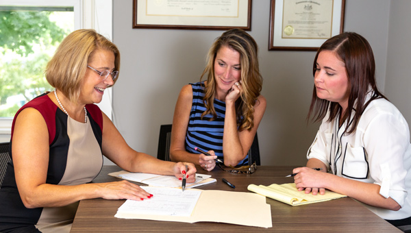 Three women meeting to review files that are spread over the table